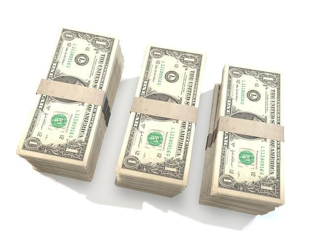 tři hromádky peněz